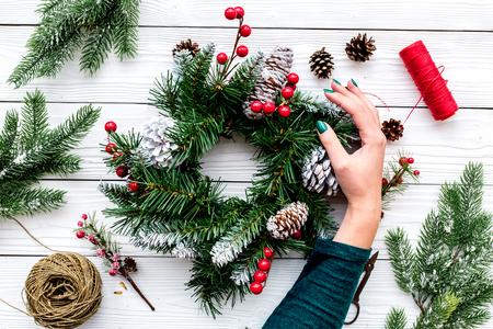 手がクリスマスリースを作る。スプルースの枝、円錐、糸、ひも、sciccors の白い木製の背景トップビュー 写真素材