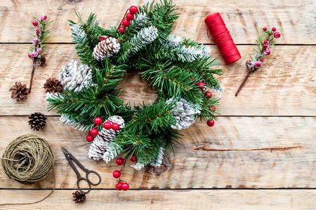 クリスマス リースを作る。小ぎれいなな枝、コーン、スレッド、麻ひも、軽い木製の背景上面にハサミを持って駆け回る 写真素材