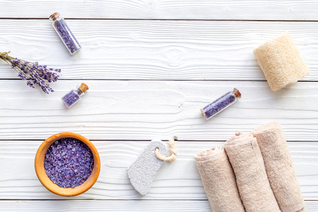 Set for foot spa with lavender. Flowers, spa salt, pumice stone, soap on white wooden background top view. Stock Photo