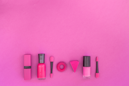 Cosmetics on colorful background. Bright pink nail polish, lipstick, eyeshadow applicator on pink background top view copyspace Banco de Imagens