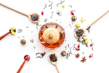 Brew tea with flowers and spices. Dried leaves and petals near tea pot on white background top view pattern.