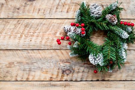 Weihnachtskranz gesponnen von den Fichtenzweigen mit roten Beeren auf hellem hölzernem Draufsicht copyspace des Hintergrundes Standard-Bild - 89844980