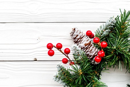 Christmas wreath woven of spruce branches with red berries on white wooden background top view closeup copyspace Stock Photo