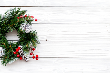 Weihnachtskranz gesponnen von den Fichtenzweigen mit roten Beeren auf Draufsichtkonzept des weißen hölzernen Hintergrundes Draufsicht Standard-Bild - 89754101
