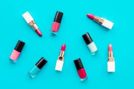 Decorative cosmetics concept. Lipsticks assorted colors and nail polish on blue background top view Stock Photo