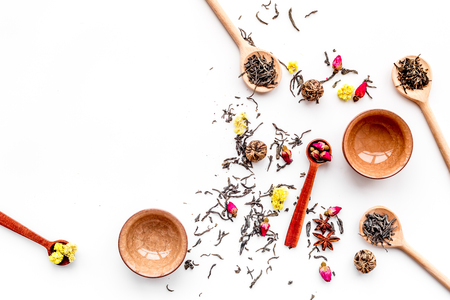 Dried tea leaves near supplements like flowers and spices on white background top view copyspace Stock Photo