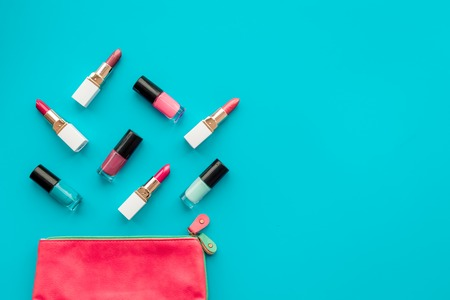 Decorative cosmetics concept. Lipsticks assorted colors and nail polish near cosmetic bag on blue background top view copyspace