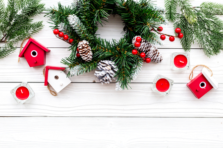 Decorate house for Christmas. Wreath and toys on white wooden background top view copyspace