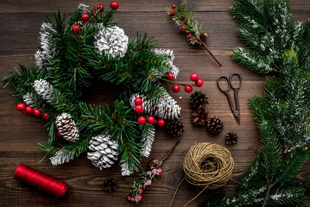 Make christmas wreath. Spruce branches, cones, threads, sciccors on wooden background top view. Stock Photo