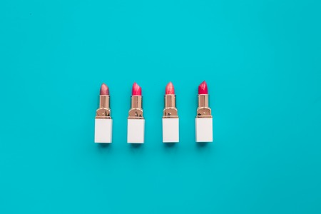 Lipsticks assorted colors on blue background top view copyspace pattern Stock Photo
