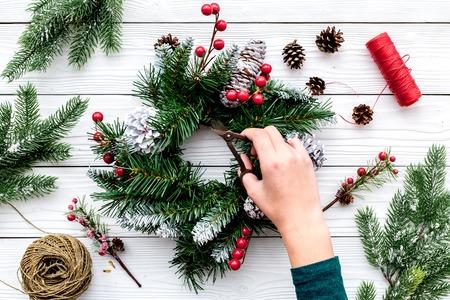 손은 크리스마스 화환을 만든다. 가문비 나무 나뭇 가지, 콘, 스레드, 꼬기, sciccors 흰색 나무 배경 상위 뷰 스톡 콘텐츠