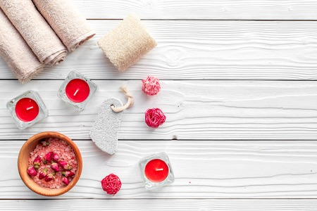 Romantic set for foot spa. Candles, salt, pumice stone, soap on white wooden background top view copyspace