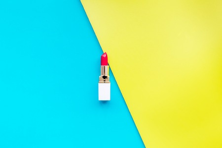 Red lipstick on yellow and blue background top view.