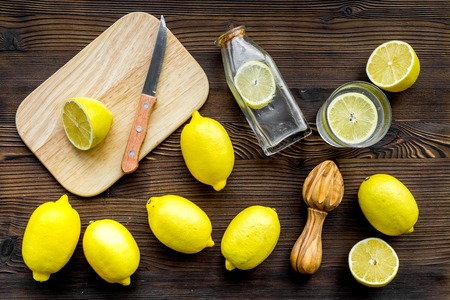 Prepare refreshing beverage lemonade. Lemons, juicer, bottle, knife, cutting board on dark wooden background top view Stock Photo