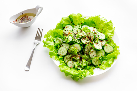 Salad with fresh cucumbers and lettuce near gravy boat. White background Stock Photo