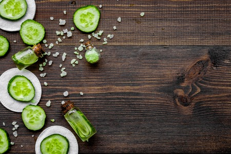 Lotion with cucumber. Dark wooden background top view copyspace