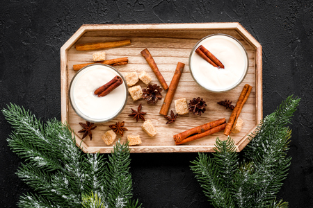Homemade classic eggnog with cinamon and badian on wooden tray near spruce branch, pinecones on black background top view