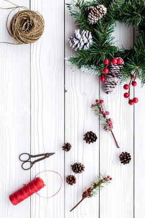 クリスマス リースを作る。小ぎれいなな枝、コーン、スレッド、麻ひも、白い木製の背景トップ ビュー copyspace のハサミを持って駆け回る