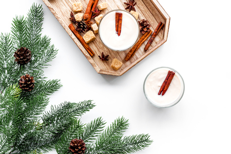 Homemade classic eggnog with cinamon and badian on wooden tray near spruce branch, pinecones on white background top view.