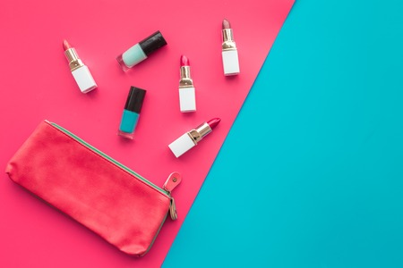 Lipsticks assorted colors and nail polish near cosmetic bag on blue and pink background top view copyspace Stock Photo