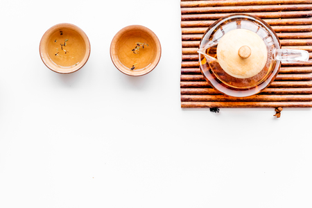 Tea ceremony concept. Tea pot, cups or bowls on white background top view copyspace