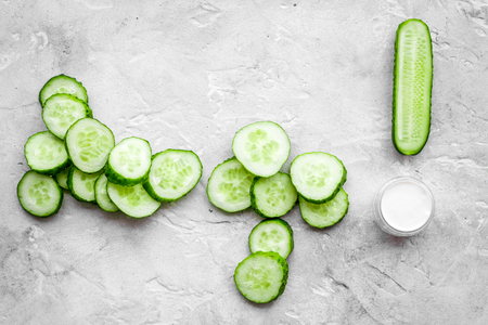 Skin care at home. Sliced cucumber on grey background top view. Stock Photo