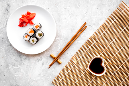 Sushi roll with salmon and avocado on plate with soy sauce, chopstick, wasabi on mat on grey stone background top view