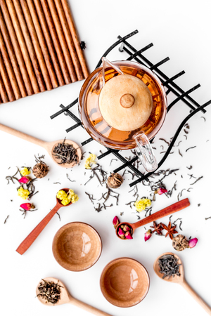 Tea party set. Tea pot, cups, dried tea leaves, fllowers, spices on wooden background top view