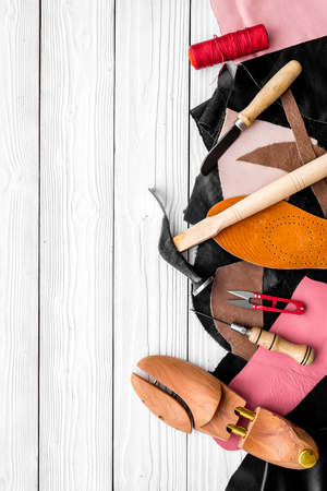 Shoemakers craft. Tools, wooden last, pieces of leather on white wooden background top view copyspace Stock fotó