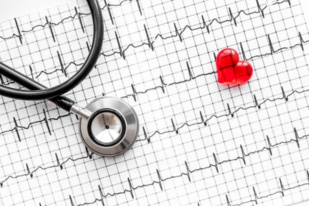 Examine the heart to prevent heart disease. Heart sign and stethoscope on cardiogram background top view