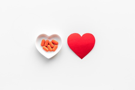 Treat heart. Pills in bowl in shape of heart on white background top view copyspace