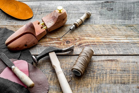 Clobbers desk. Tools, wooden last, pieces of leather on wooden background copyspace Stock Photo