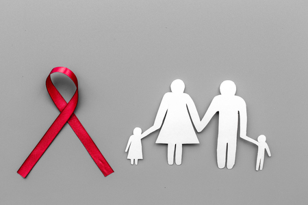 Red ribbon for HIV, AIDS, substance-abuse and anorexia awareness near paper silhouette of family on grey background top view copyspace