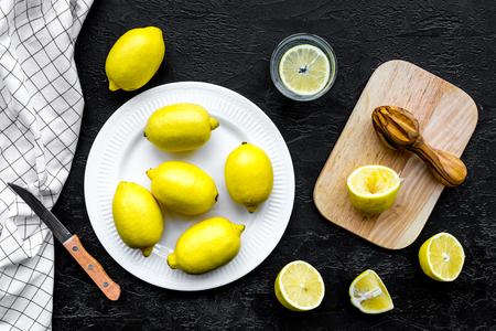 Make lemonade at home. Lemons, juicer, glass for beverage, knife, cutting board on black background top view