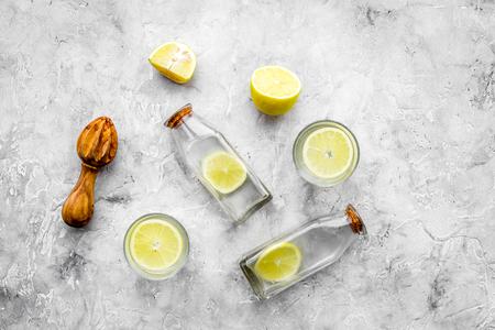 Fresh homemade lemonade. Lemons, juicer, glass for beverage on grey stone background top view copyspace