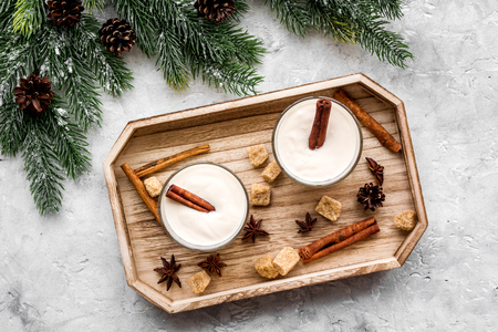 Homemade classic eggnog with cinamon and badian on wooden tray near spruce branch, pinecones on grey stone background top view Stock Photo