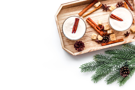 Homemade classic eggnog with cinamon and badian on wooden tray near spruce branch, pinecones on white background top view copyspace