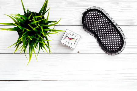 Healthy sleep concept. Sleep mask, plant, alarm clock on white wooden background top view copyspace Stock Photo