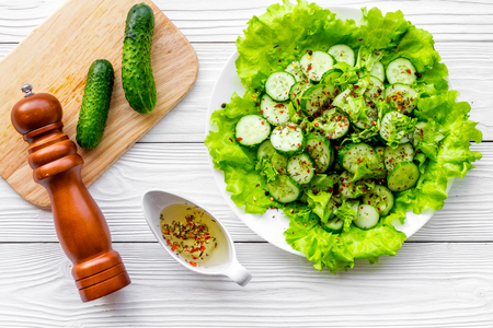 Salad with fresh cucumbers and lettuce near paperbox and gravy boat. Grey wooden background top view