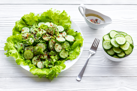 Salad with fresh cucumbers and lettuce near gravy boat. Grey wooden background