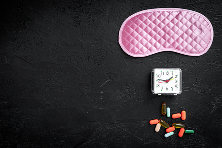 Combat insomnia. Sleeping pills near sleep mask and alarm clock on black background top view copyspace Banco de Imagens