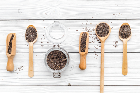 Superfood chia seeds in a wooden spoon and scoop on white wooden background top view