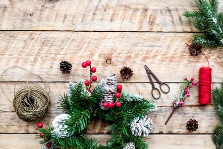 Machen Sie Weihnachtskranz. Fichtenzweige, Kegel, Threads, Schnur, Sciccors auf Draufsicht des hellen hölzernen Hintergrundes Standard-Bild - 89907529