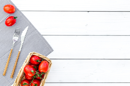 Tomatoes for picnic on tablecloth on white wooden background top view copyspace