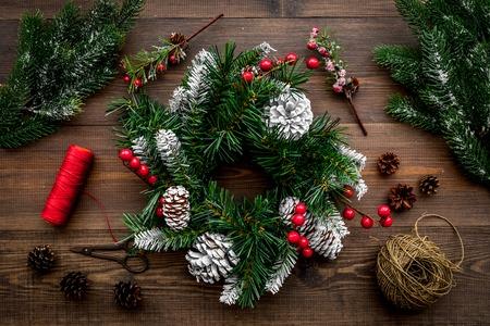 Machen Sie Weihnachtskranz. Gezierte Zweige, Kegel, Threads, Sciccors auf Draufsicht des hölzernen Hintergrundes Standard-Bild - 89907496