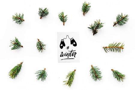 Hello winter hand lettering with mittens icon. Winter pattern with spruce branches on white background top view