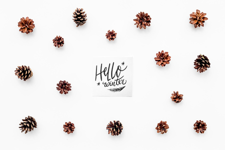 Hello winter hand lettering. Winter pattern with pinecones on white background top view Imagens - 89907506
