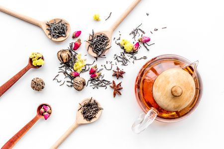 Brew tea with flowers and spices. Dried leaves and petals near tea pot on white background top view pattern Stock Photo