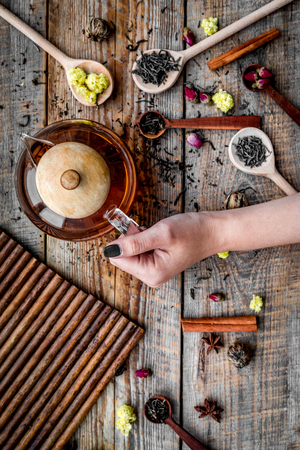 Brew tea with flowers and spices. Hand hold tea pot on wooden background top view Stock Photo