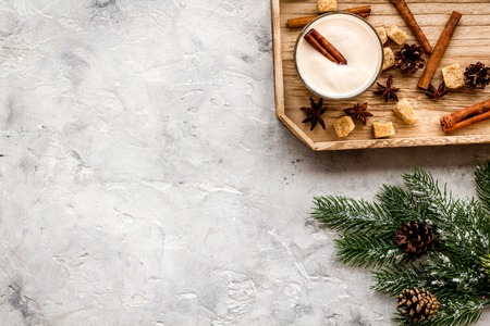 Homemade classic eggnog with cinamon and badian near spruce branch, pinecones, gingerbread on grey stone background top view copyspace Stock Photo